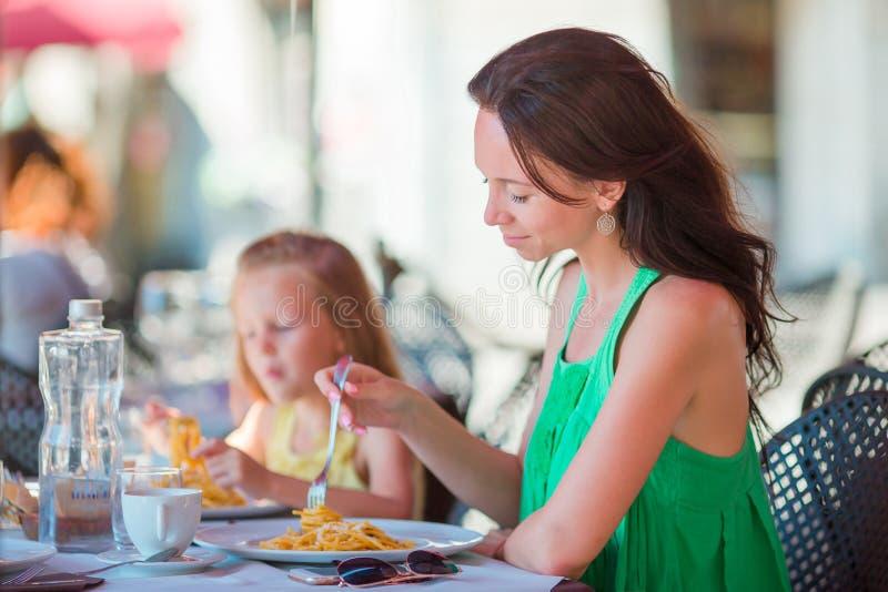 Familie die diner hebben bij openluchtkoffie met Italiaans menu Aanbiddelijke meisje en moeder die spaghetti op luxehotel eten royalty-vrije stock foto's