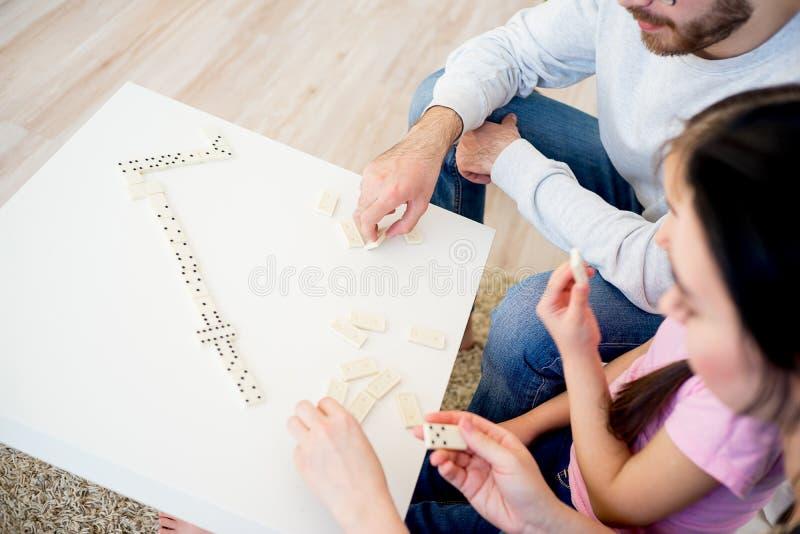 Familie, die Domino spielt stockbild