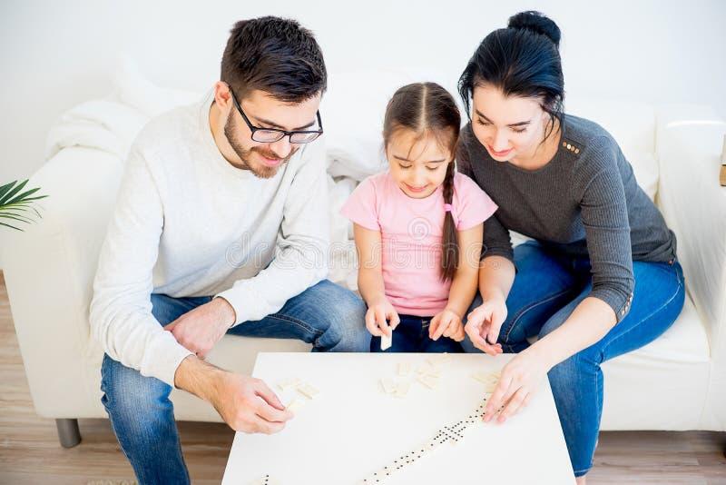 Familie, die Domino spielt lizenzfreie stockbilder