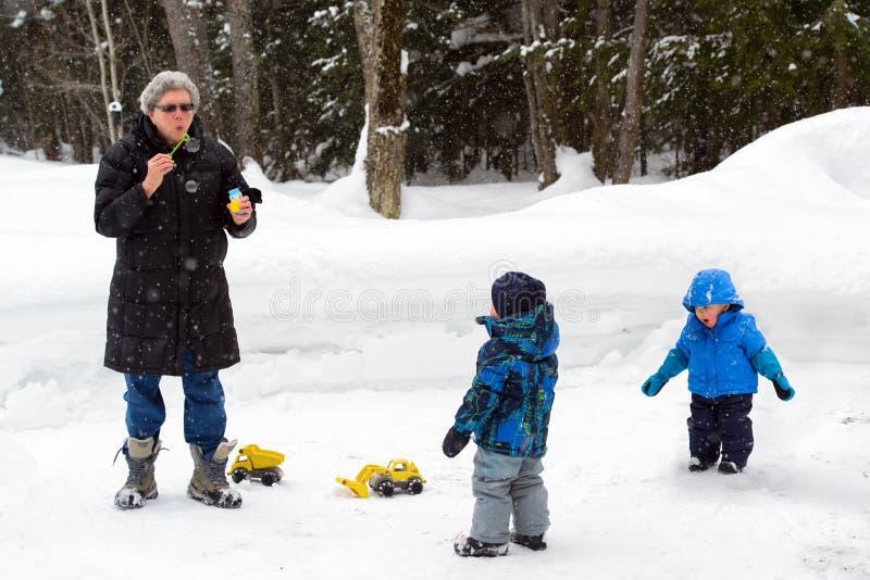 Familie, die draußen im Winter spielt lizenzfreies stockbild