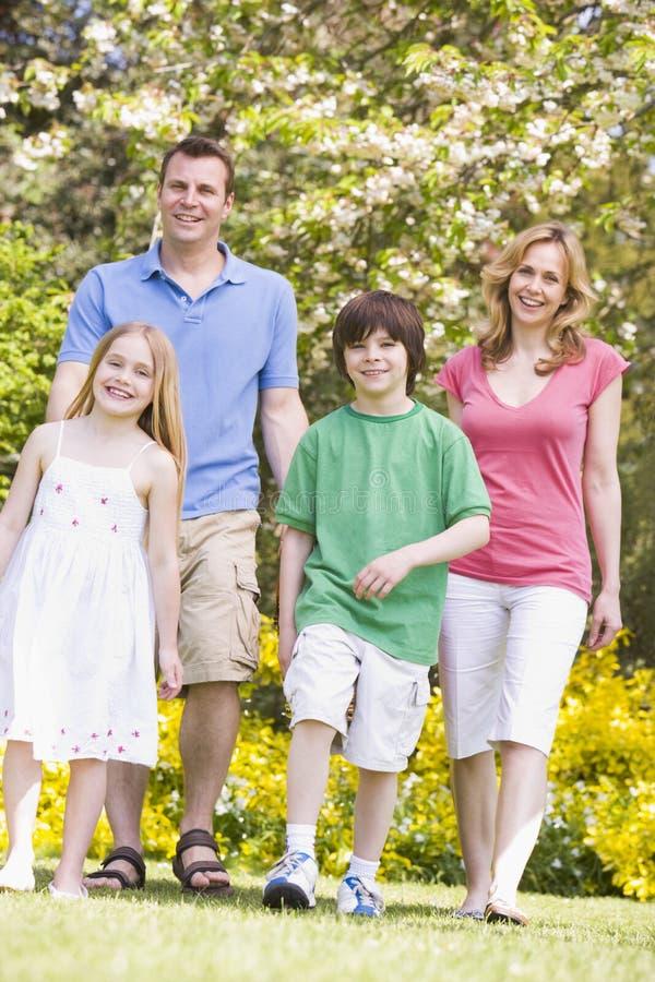 Familie, die draußen lächelnd geht lizenzfreie stockfotos