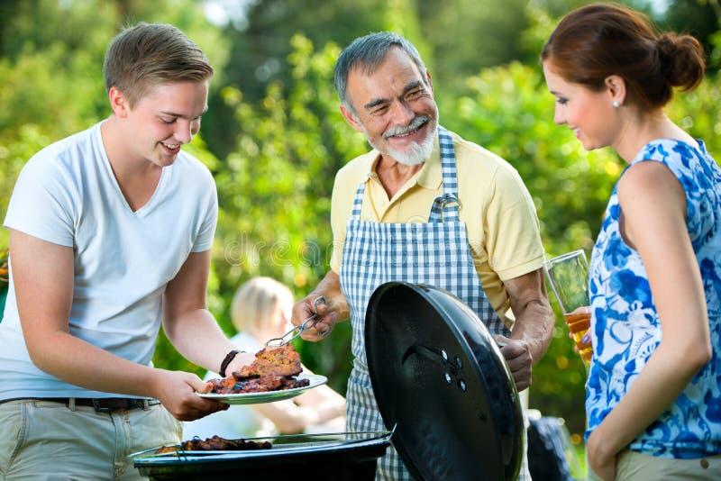 Familie die een barbecuepartij heeft royalty-vrije stock afbeeldingen