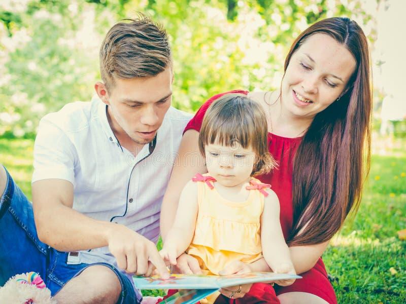 Familie die een boek lezen bij park royalty-vrije stock afbeeldingen