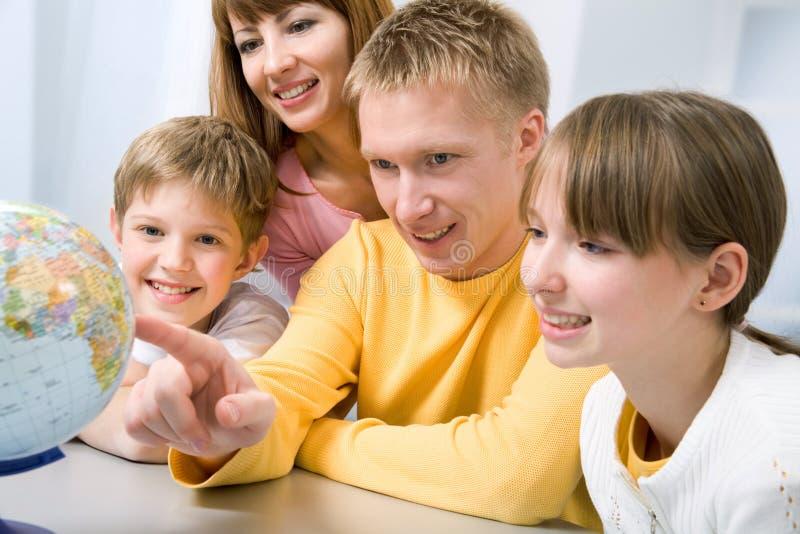 Familie die een bol onderzoekt stock afbeeldingen