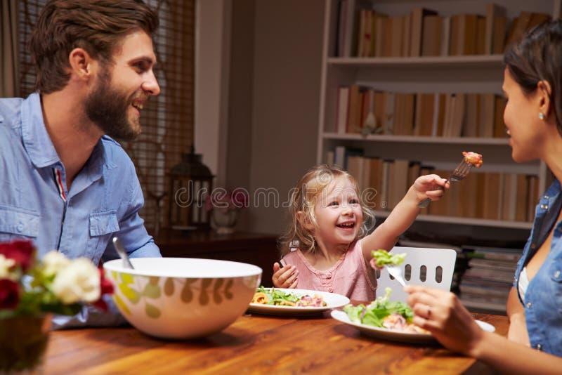 Familie die een diner eten bij een eettafel stock foto