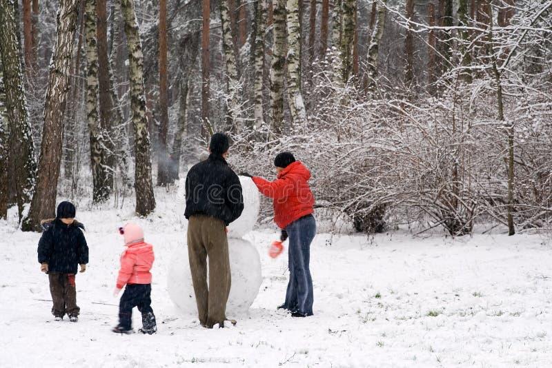 Familie die een Mens van de Sneeuw vormt stock foto's