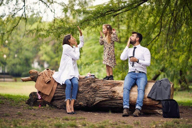 Familie die een onderbreking in park na school en het werk hebben stock afbeeldingen