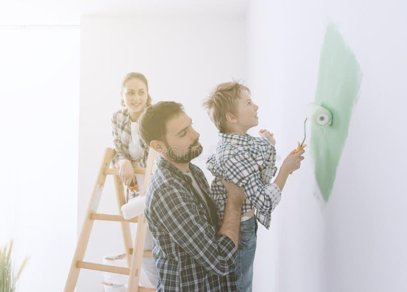 Familie die een ruimte samen schilderen stock afbeeldingen