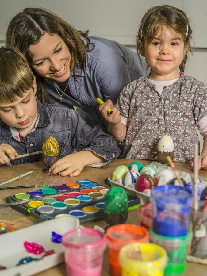 Familie die eieren verfraaien voor Pasen stock fotografie