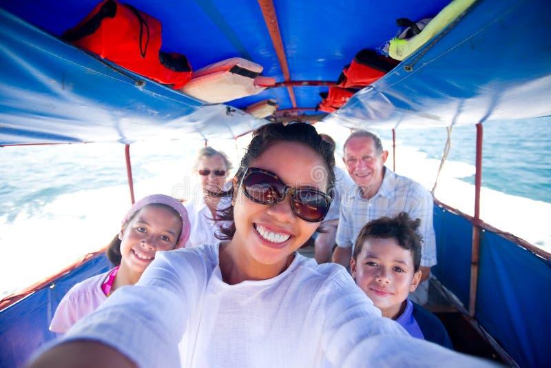 Familie, die ein fettes Boot geht zu einer Insel reitet. lizenzfreie stockfotografie