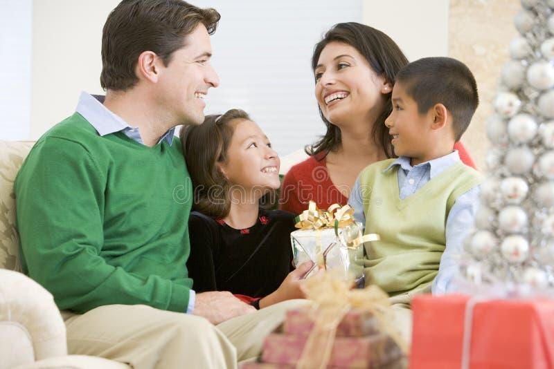 Familie, die an einander, Geschenke anhalten lächelt lizenzfreie stockfotos
