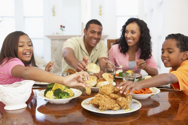 Familie, die eine Mahlzeit zu Hause hat lizenzfreie stockfotografie