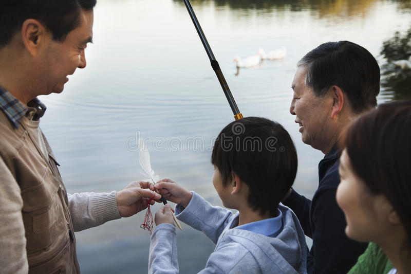 Familie, die einem Jungen beibringt, wie man an einem See fischt stockfotos