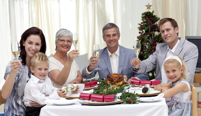 Familie, die in einem Weihnachtsabendessen tusting ist stockfotos
