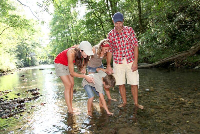 Familie, die einen Fluss kreuzt stockbilder