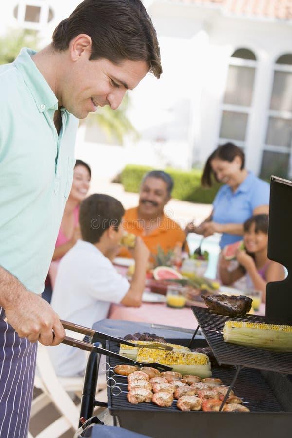 Familie, die einen Grill genießt lizenzfreie stockbilder