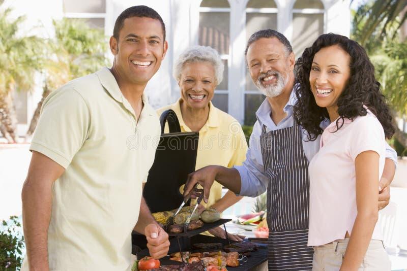 Familie, die einen Grill genießt lizenzfreies stockbild