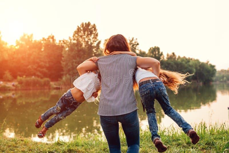 Familie die en pret spelen hebben door de zomerrivier bij zonsondergang Moederholding en in openlucht het spinnen rond dochters stock foto