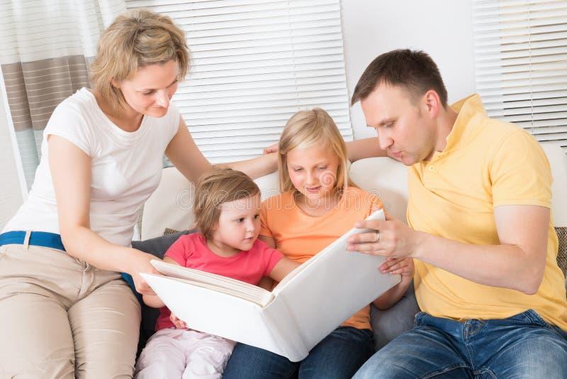 Familie, die Fotos in Photobook betrachtet stockfotos