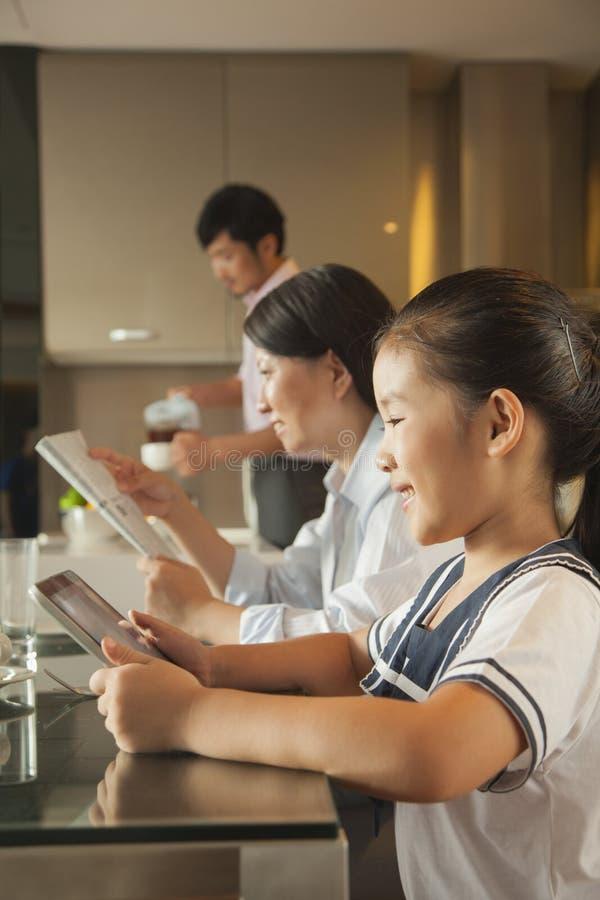 Familie, die Frühstück isst und digitale Tablette verwendet stockfoto