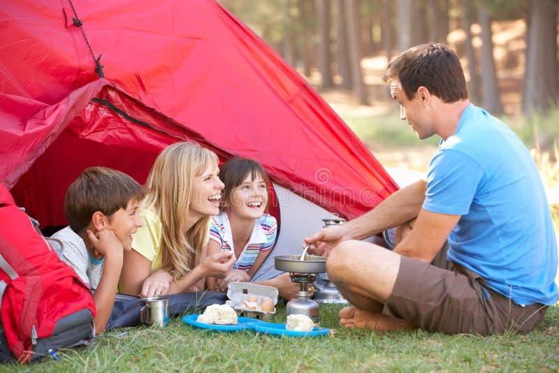 Familie, die Frühstück an kampierendem Feiertag kocht stockfoto