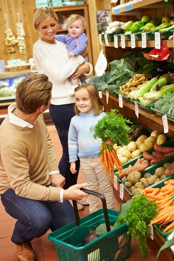 Familie, die Frischgemüse im Bauernhof-Shop wählt stockbild