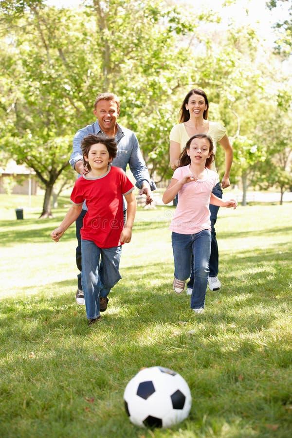 Familie, die Fußball im Park spielt lizenzfreie stockbilder