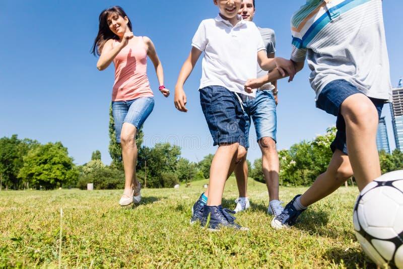 Familie, die Fußball oder Fußball im Park im Sommer spielt lizenzfreies stockfoto