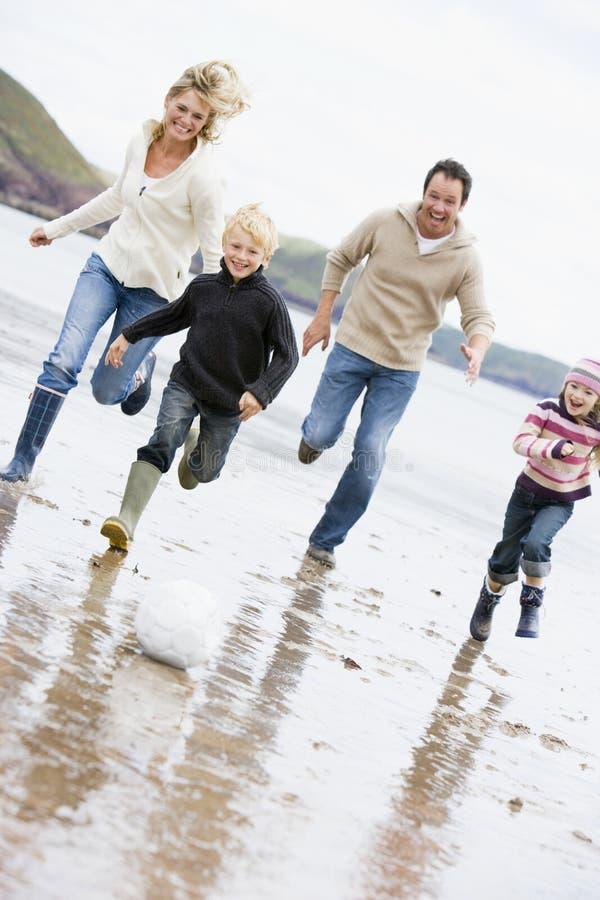Familie, die Fußball am Strandlächeln spielt