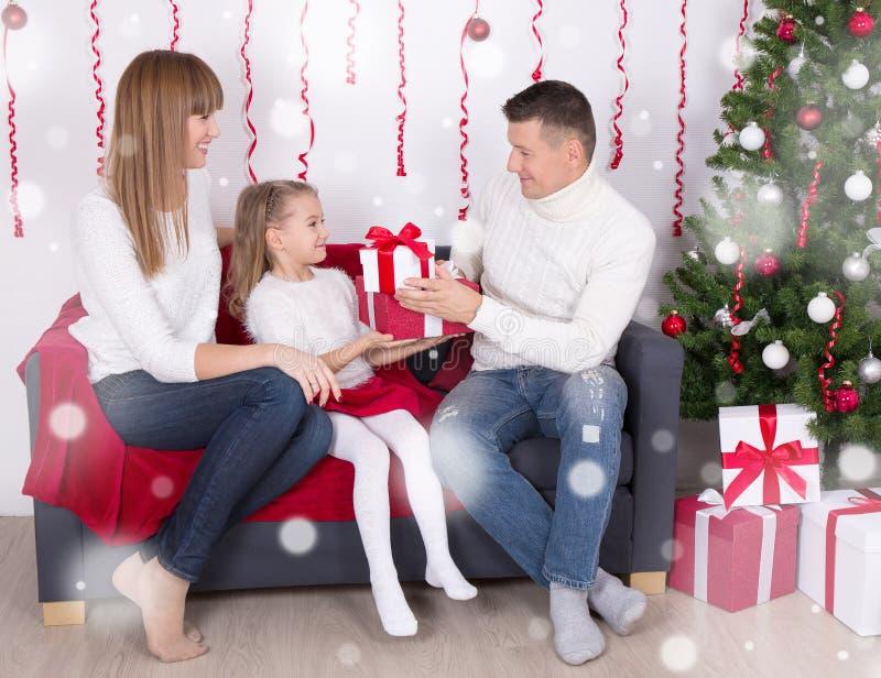 Familie, die Geschenke vor Weihnachtsbaum austauscht stockfotografie