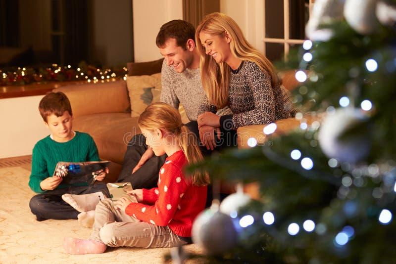 Familie die Giften opvouwt door Kerstboom