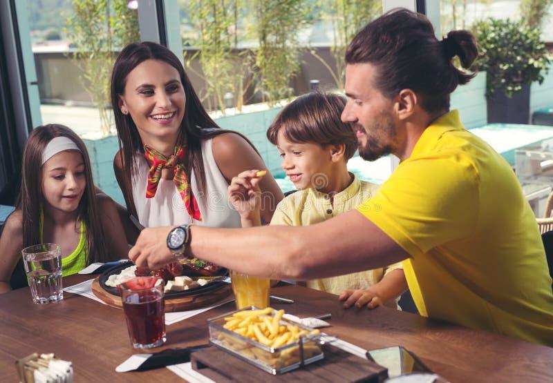 Familie die grote tijd in een restaurant hebben stock afbeeldingen
