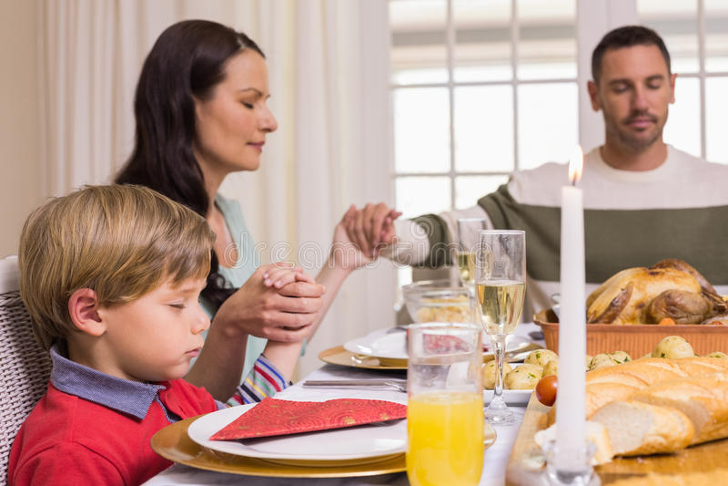 Familie die gunst zeggen vóór Kerstmisdiner stock fotografie