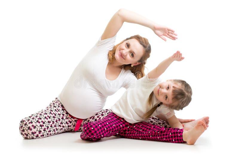 Familie die gymnastiek doen Zwangere vrouw met dochter die het uitrekken op vloer uitoefenen zich stock afbeeldingen