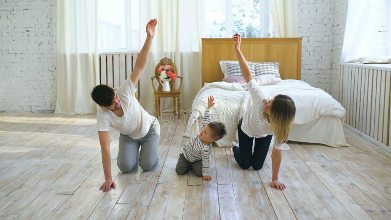 Familie die gymnastiek- oefeningen in slaapkamer doen thuis - gezond het levensonderwijs stock foto's