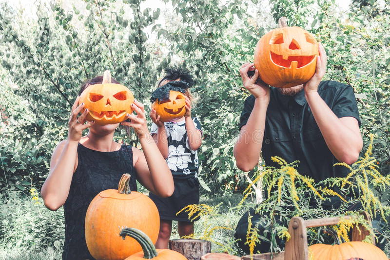 Familie, die Halloween-Kürbis vor ihren Gesichtern, Vorbereitung für Partei im Garten nahe Jack-O-Laternendekorationen hält fett stockfotos