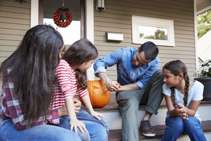 Familie die Halloween-Pompoen op Huisstappen snijden royalty-vrije stock fotografie