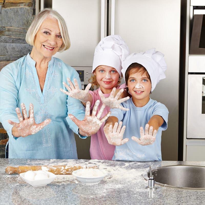 Familie die handen met bloem in keuken tonen stock foto's