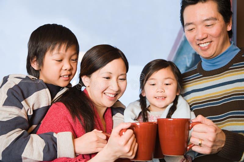 Familie, die heiße Getränke hat stockfotografie