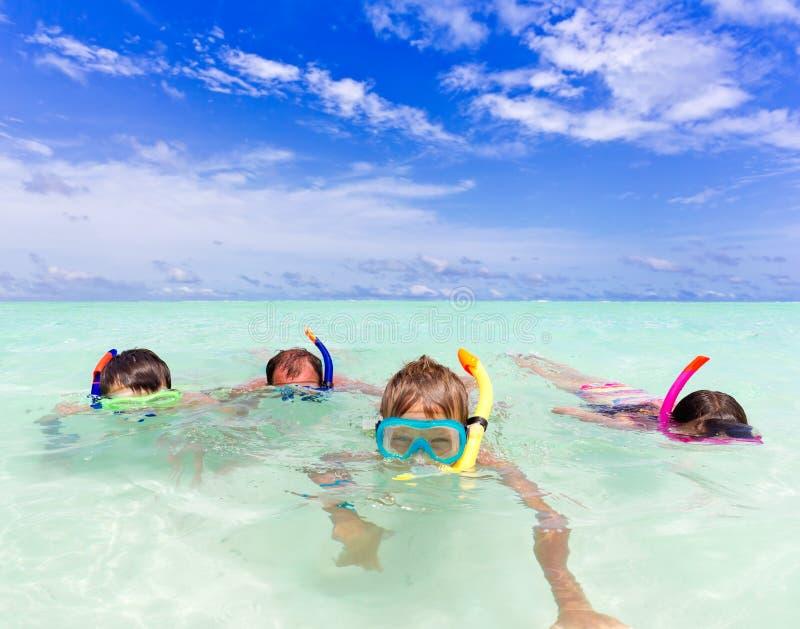 Familie die in het water snorkelt stock foto's