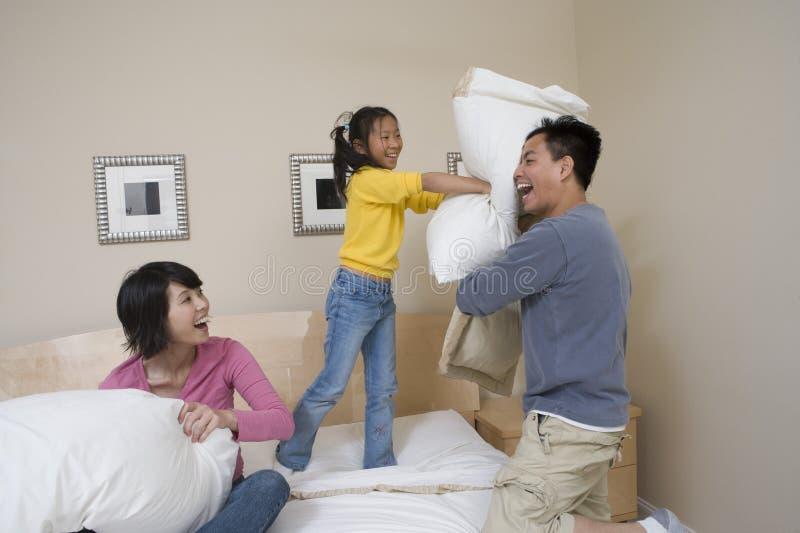 Familie die Hoofdkussenstrijd in Bed hebben stock afbeeldingen