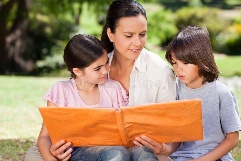 Familie die hun albumfoto bekijkt stock afbeeldingen