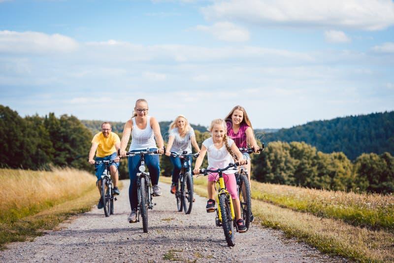 Familie die hun fietsen berijden op middag in het platteland royalty-vrije stock foto