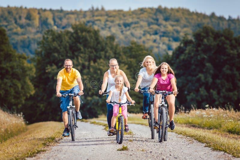 Familie die hun fietsen berijden op middag in het platteland royalty-vrije stock foto's