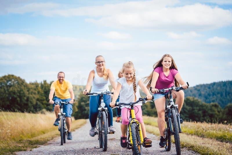 Familie die hun fietsen berijden op middag in het platteland royalty-vrije stock afbeeldingen