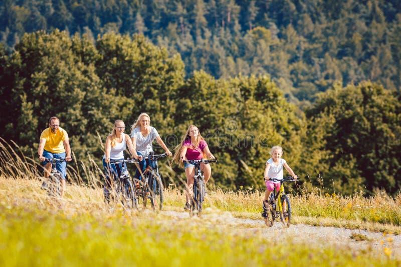 Familie die hun fietsen berijden op middag in het platteland stock afbeelding