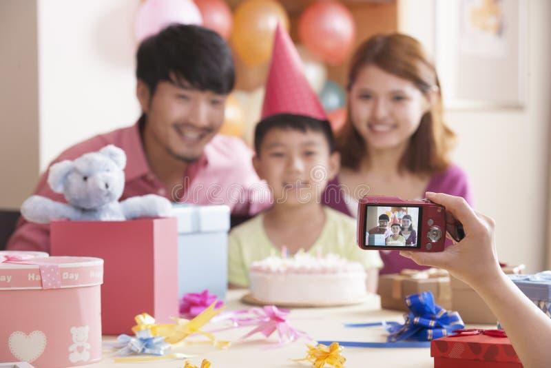 Familie, die ihr Foto am Geburtstag ihres Sohns machen lässt lizenzfreie stockfotos