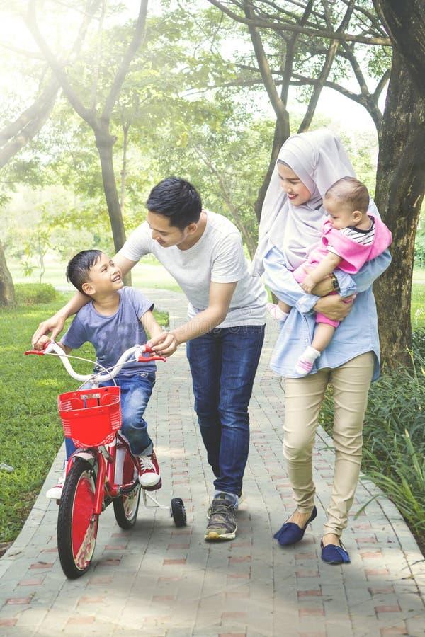 Familie, die ihren Sohn unterrichtet, ein Fahrrad zu reiten stockbild