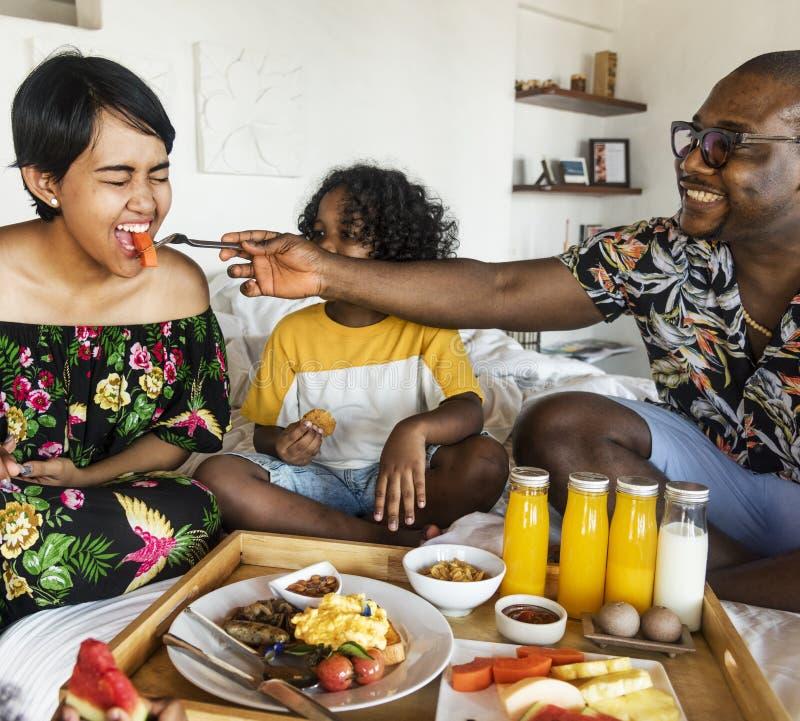 Familie, die im Bett frühstückt stockbild