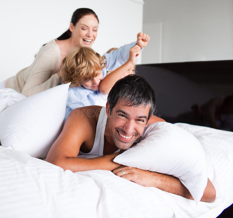 Familie, die im Bett spielt lizenzfreies stockbild